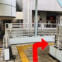 階段を上ったらそのまま真っすぐ進み、エレベーターと壁に書いている箇所を右に曲がります。